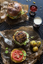 Homemade juicy pork burger a veggie one with a flag topper and buttered baby potatoes with dill black background moody atmosphere Royalty Free Stock Photo
