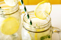Homemade lemonade in mason jars with big green paper straw Stock Images