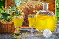 Homemade liqueur made ​​of honey and lime on old wooden table Stock Image