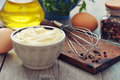 Homemade mayonnaise in bowl with oil eggs and spice on wooden background Royalty Free Stock Photography