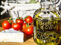 Homemade olive oil fresh in handmade bottle with french soft cheese and small tomatoes Stock Photo