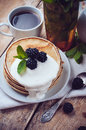 Homemade pancakes with blackberries a stack of fresh and whipped cream on a wooden table a healthy breakfast close up Royalty Free Stock Images