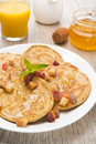 Homemade pancakes with peaches and honey for breakfast on plate the vertical Royalty Free Stock Photo