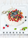 Homemade Pavlova cake with fresh garden berries and silver spoons on white baking tray over light wooden background Royalty Free Stock Photo