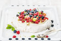 Homemade Pavlova cake with fresh garden and forest berries on white baking tray over light backdrop Royalty Free Stock Photo