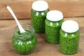 Homemade pesto in jars on rustic wooden table
