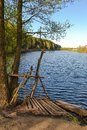 Homemade pier for fishermen from the thick branches on the lake. Royalty Free Stock Photo