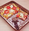 Homemade pizza on a baking tray sliced with a cutter knife on a wooden board Stock Photo