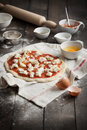 Homemade pizza dough stretched and uncooked with tomato sauce and mozzarella on a kitchen towel ready for ingredients taken on a Royalty Free Stock Images