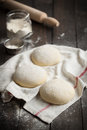 Homemade pizza dough three floured balls of uncooked on a kitchen towel on a rustic dark wooden table with flour and rolling pin Royalty Free Stock Photos