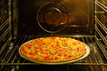 Homemade pizza in oven Royalty Free Stock Images