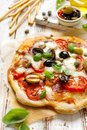 Homemade pizza with tomatoes, olives, salami, mozzarella cheese and fresh basil on a wooden rustic table Royalty Free Stock Photo