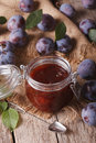Homemade plum confiture in a glass jar close up vertical top view on the table Stock Photo
