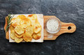 Homemade potato chips with sea salt and herb on cutting board Royalty Free Stock Photo