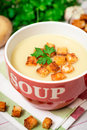 Homemade potato cream soup with croutons and parsley in red bowl on table Royalty Free Stock Photo