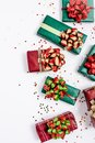 Red and green gifts with paper kraft bows and star confetti on white background with copy space. View from the top. Close up