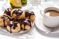 Homemade profiteroles with chocolate cream on the white background Stock Image