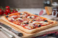 Homemade rectangular pizza on a rustic table pepperoni with ingredients Royalty Free Stock Image