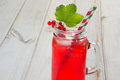 Homemade red currant lemonade in a mason jar and garnish of berry branch on ligth wooden table. Royalty Free Stock Photo