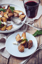 Homemade rustic dinner a glass of wine and a baked potato with soft cheese fresh basil in white plate on wooden board Stock Images
