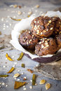 Homemade rustic muffins with pumpkin chocolate and oat flakes on bowl with burnt greasproof paper vintage background Stock Photo