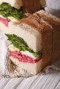 Homemade sandwiches with salami wrapped in paper vertical macro Royalty Free Stock Photo