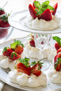 Homemade small strawberry pavlova meringue cakes with mascarpone cream and fresh mint leaves Royalty Free Stock Photo