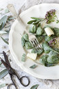 Homemade spinach dumplings with sage leafs, butter curls, flowers on plate on rustic background Royalty Free Stock Photo