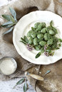 Homemade spinach dumplings with sage leafs and flowers on plate on rustic background Royalty Free Stock Photo