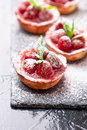 Homemade strawberries tarts with powdered sugar on slate plate, black background. Close up. Royalty Free Stock Photo