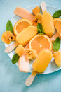 Homemade summer treat orange popsicles with fresh fruits and edible flowers Stock Images