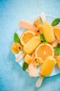 Homemade summer treat orange popsicles with fresh fruits and edible flowers Royalty Free Stock Photography