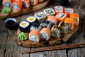 Homemade sushi with salmon, tobiko caviar, omelet, cucumber, sesame and soft cheese. Rustic style. Royalty Free Stock Photo