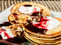 Homemade sweet pancakes with fruit jam, sour cream on a white plate. Breakfast with stack topped blueberry jam and Royalty Free Stock Photo