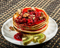 Homemade sweet pancakes with raspberry jam on a white plate. Breakfast with stack topped blueberry jam, walnuts and kiwi Royalty Free Stock Photo