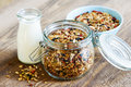 Homemade toasted granola in open glass jar and milk or yogurt on rustic wooden background Royalty Free Stock Photography