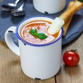 Homemade tomato basil soup in the mug, served with mozzarella cheese stick and croutons, square Royalty Free Stock Photo