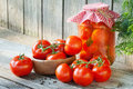 Homemade tomatoes in glass jar fresh and canned on wooden board Stock Image