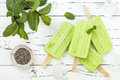 Homemade vegan green tea matcha mint coconut milk popsicles with chia seeds on rustic white wooden background