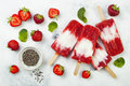Homemade vegan strawberry coconut milk popsicles with chia seeds on rustic white background. Royalty Free Stock Photo