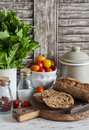 Homemade whole grain bread, fresh green salad and tomatoes on a light rustic wood background. Royalty Free Stock Photo