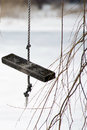 Homemade wooden swing on rope close up near tree branches over frozen lake in the wintertime Royalty Free Stock Photos