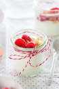 Homemade yogurt dessert with raspberries and crushed cookies in a small jar on a kitchen background Royalty Free Stock Photo
