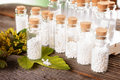 Homeopathic globules lactose sugar in glass bottles with plants Royalty Free Stock Images