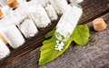 Homeopathic globules lactose sugar on leaf with glass bottle Stock Images