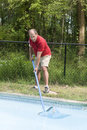 Homeowner cleaning swimming pool Royalty Free Stock Photo