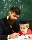 Homeschooling concept. Father checking homework, helps to boy, son. Teacher in formal wear and pupil in mortarboard in Royalty Free Stock Photo