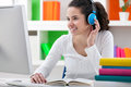 Homework with headphones teen girl doing her online and listening to Stock Image
