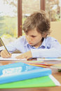 Homework little schoolboy bored of writing his at home Royalty Free Stock Images