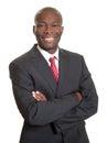 Homme d affaires africain avec les bras croisés riant de l appareil photo Photographie stock libre de droits